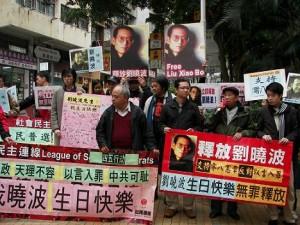 """图一:前往中联办请愿的人士在香港西区警署前集会,手持书有""""刘晓波生日快乐""""、""""立即释放刘晓波"""""""